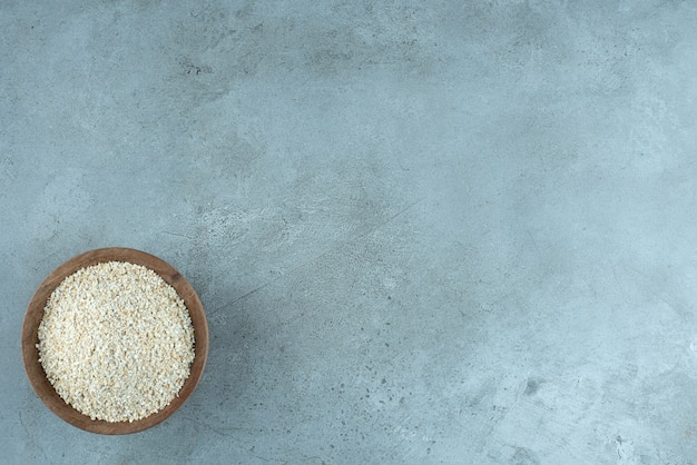 Grãos de trigo ou arroz em um copo de madeira com fundo azul. foto de alta qualidade
