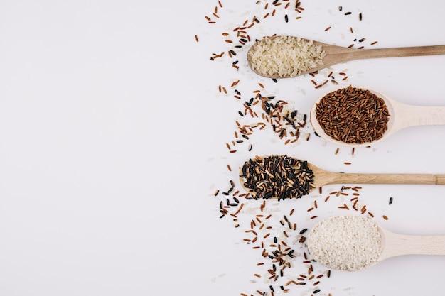 Grãos derramados em torno de colheres com arroz