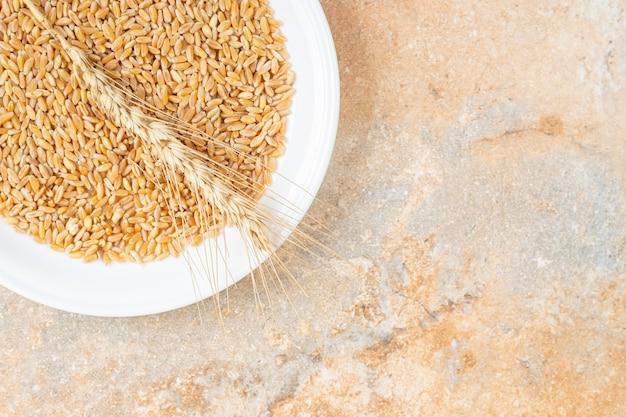 Grãos e espigas de trigo em um prato, no mármore.