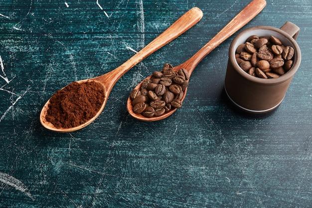 Grãos e pó de café em colheres de pau.