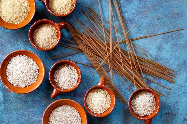 Grãos e sementes em tigelas de cerâmica e espaguete integral. comida vegetariana. vista do topo. copie o espaço