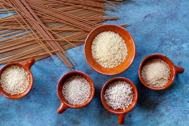 Grãos e sementes em tigelas de cerâmica e espaguete integral