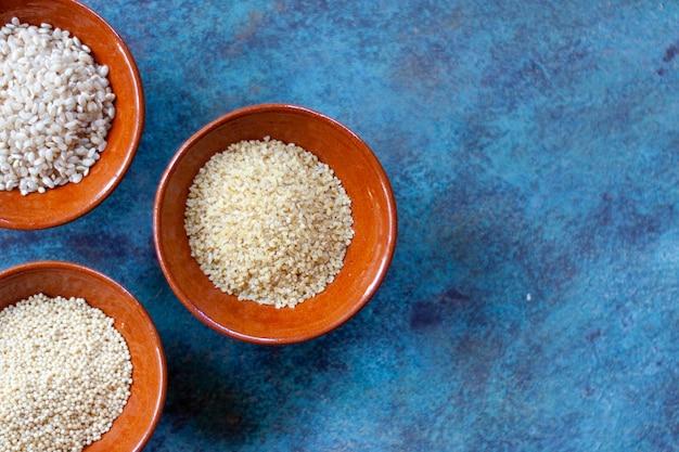 Grãos e sementes em tigelas de cerâmica