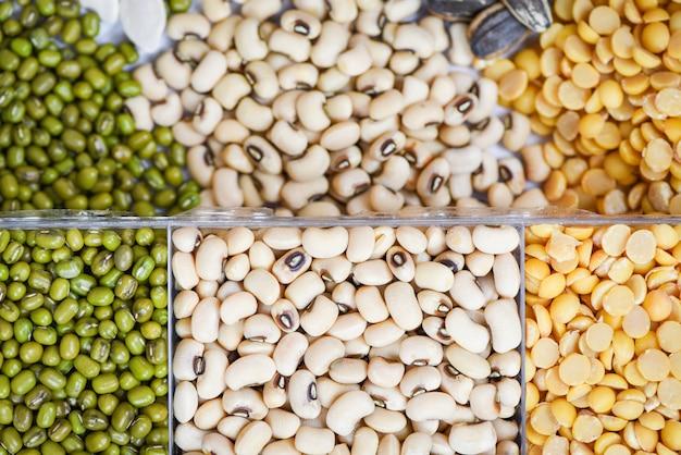 Grãos integrais feijão e leguminosas sementes lentilhas fundo vista superior - vários feijões de colagem misturam agricultura de ervilhas de alimentos saudáveis naturais para cozinhar ingredientes feijões mungos, feijão de soja, ervilhas de olhos pretos