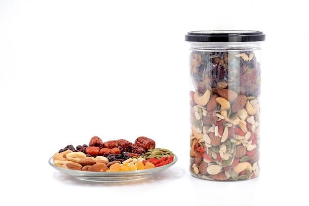 Grãos inteiros e frutas secas em uma placa de vidro e uma garrafa de plástico, isolada no fundo branco.
