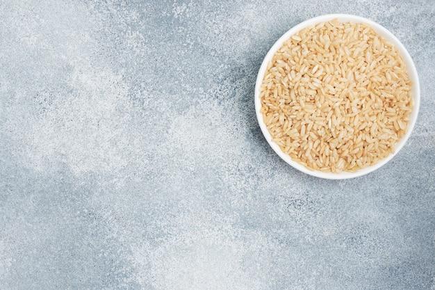 Grãos longos crus de arroz integral em um prato, espaço de cópia de plano de fundo cinza, vista superior.