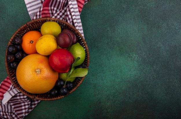 Grapefruit com limão, limão, pêssego, cereja, ameixa, laranja e ameixa em uma cesta sobre um fundo verde.