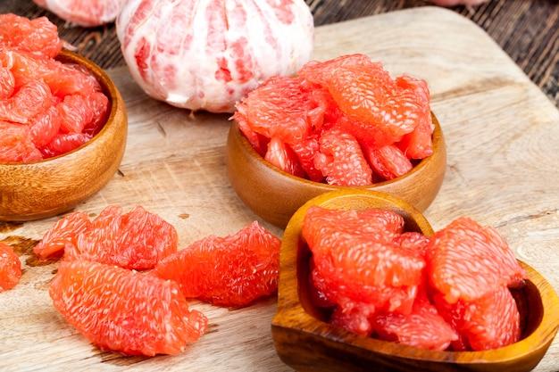 Grapefruit madura azeda descascada e dividida em fatias, toranja rosa pronta para comer, close-up Foto Premium