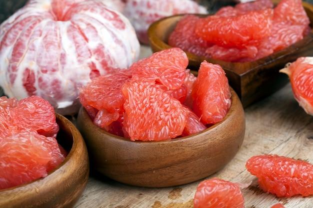 Grapefruit madura azeda descascada e dividida em fatias, toranja rosa pronta para comer, close-up