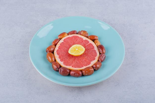 Grapefruit madura fatiada, limão e amoras prateadas na placa azul.