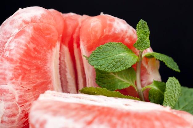 Grapefruit vermelha suculenta e deliciosa em fatias, agridoce e hortelã verde