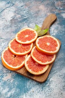 Grapefruits de corte de vista inferior na tábua de corte na superfície branca e azul