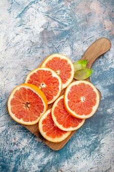 Grapefruits de corte de vista superior em uma placa de corte na superfície branca e azul