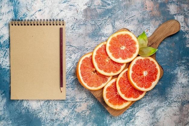 Grapefruits de corte de vista superior no caderno de tábua e lápis na superfície branca azul