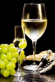 Grappa de vidro com copo de vinho turva em fundo preto