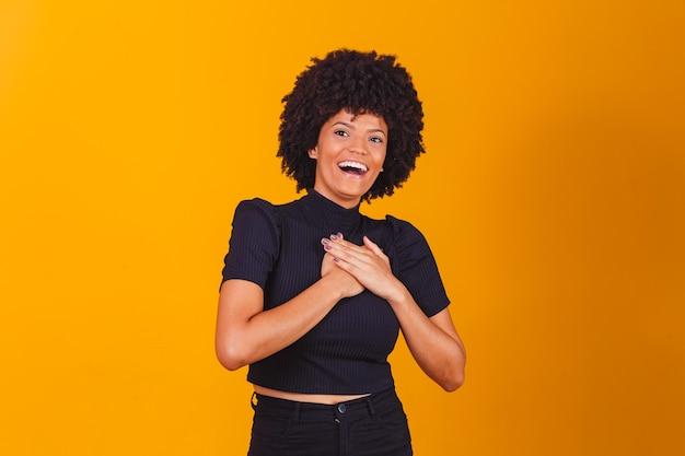 Grata, esperançosa, feliz, mulher negra de mãos dadas no peito, sentindo-se satisfeita, agradecida, sincera senhora africana expressando amor sincero