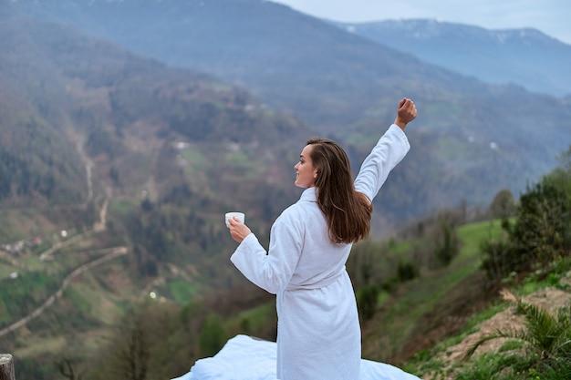 Grátis uma mulher viajante relaxada vestindo roupão de banho com os braços abertos, bebendo café e apreciando a paisagem da montanha. momento calmo e tranquilo do conceito de desejo por viagens quando a pessoa sente felicidade e liberdade