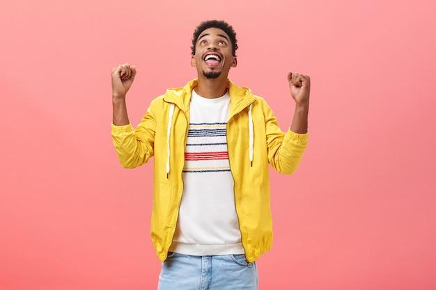 Grato, feliz e entusiasmado jovem estudante afro-americano levantando os punhos olhando para cima, satisfeito por ser abençoado por deus, comemorando o término bem-sucedido dos exames sobre o fundo rosa