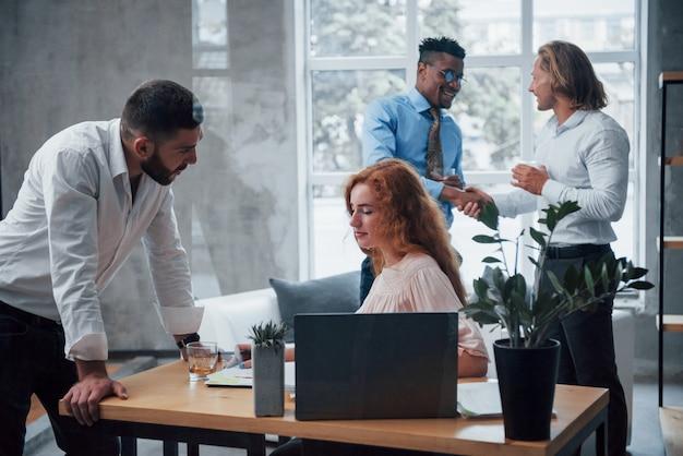 Grato humor por trás. equipe de negócios jovem trabalhando em um projeto com o laptop na mesa e sorrindo