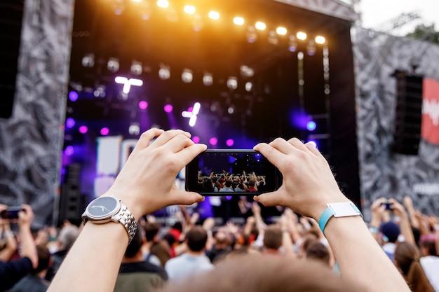 Gravação de concerto por smartphone. celular em mãos levantadas