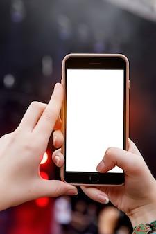 Gravação de concerto por smartphone. telefone móvel nas mãos levantadas. tela em branco