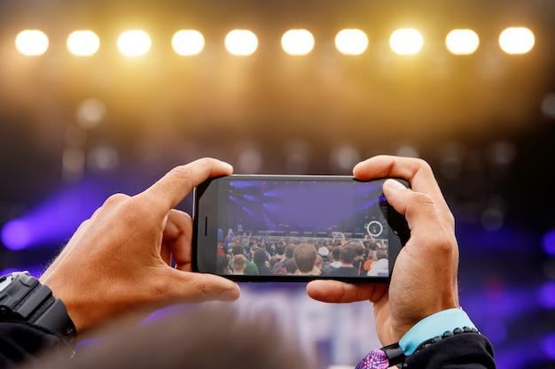 Gravação de vídeo ou foto em um show. smartphone nas mãos.