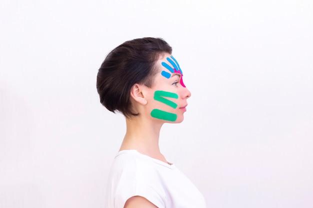 Gravação facial, close-up do rosto de uma garota com fita cosmética anti-rugas