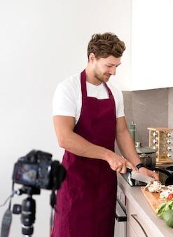 Gravação masculina considerável enquanto cozinha em casa