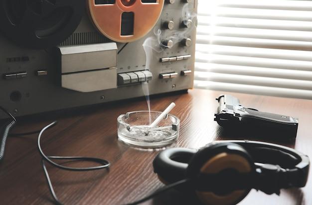 Gravador de fita de carretel para escuta telefônica. conversas de espionagem da kgb. arma preta próxima. cinzeiro com um cigarro.