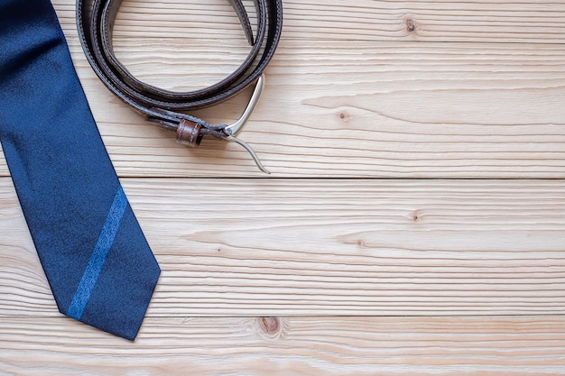 Gravata azul com cinto em fundo de madeira com espaço de cópia para o texto.