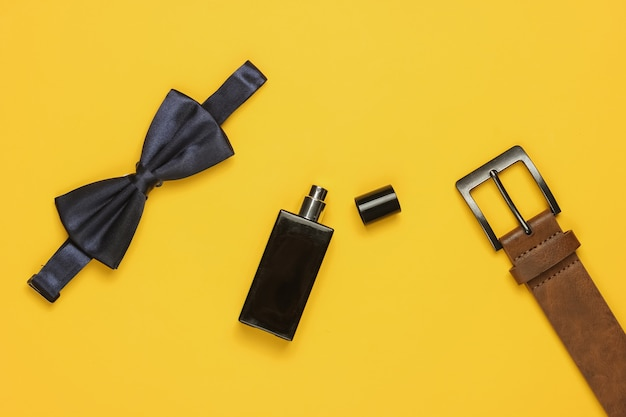 Gravata borboleta, cinto, frasco de perfume em fundo amarelo. acessórios masculinos, conjunto de estilo empresarial para homens. estilo formal, preparando-se para o casamento.