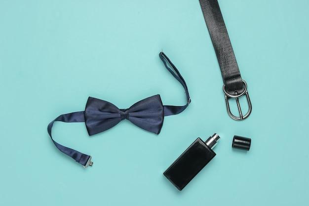 Gravata borboleta, cinto, frasco de perfume em um fundo azul. acessórios masculinos, conjunto de estilo empresarial para homens. estilo formal, preparando-se para o casamento.