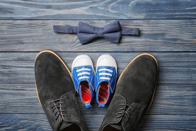 Gravata borboleta com sapatos para pai e filho na mesa de madeira