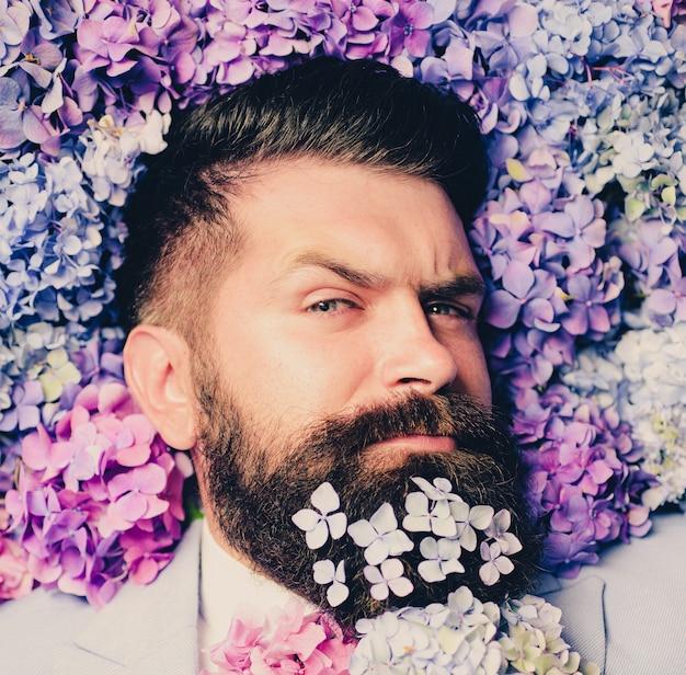 Gravata borboleta de flores. homem de negócios elegante com traje clássico. homem de terno azul. homem barbudo e