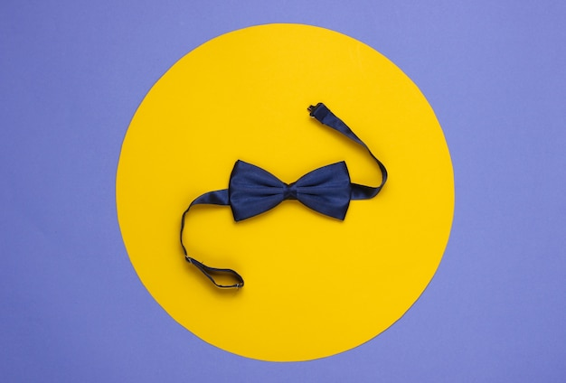 Gravata borboleta em papel roxo com um círculo amarelo no meio.