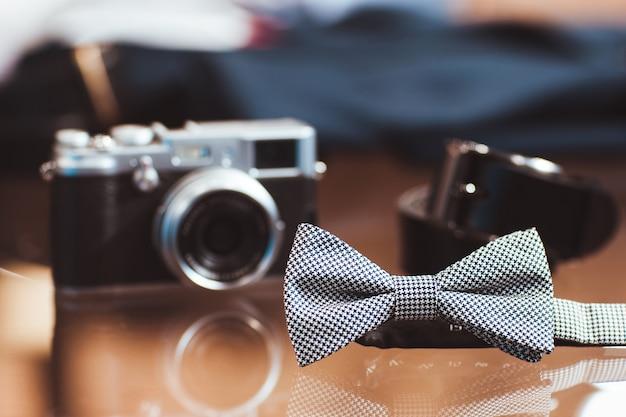 Gravata borboleta masculina padrão houndstooth câmera fotográfica desfocada e cinto