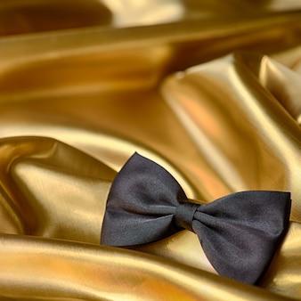 Gravata-borboleta preta sobre fundo de tela dourada