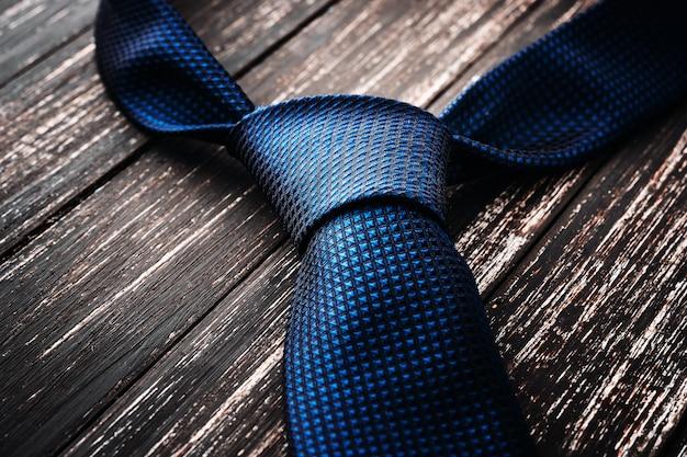 Gravata masculina azul sobre fundo preto de madeira