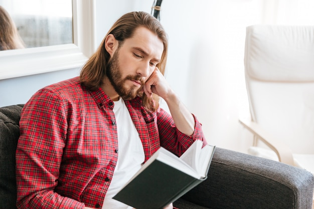 Grave barbudo jovem sentado e lendo o livro em casa