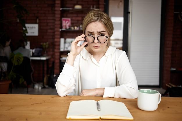 Grave bela jovem empregador feminino vestindo camisa branca e óculos, realizando entrevista de emprego enquanto está sentado no escritório com o diário aberto e uma xícara de café na mesa de madeira. negócios e carreira