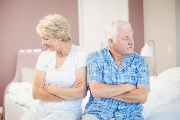 Grave casal sênior sentado na cama em casa
