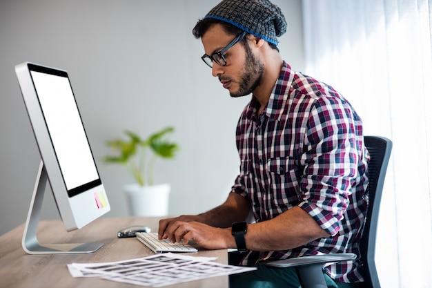 Grave casual homem trabalhando na mesa do computador