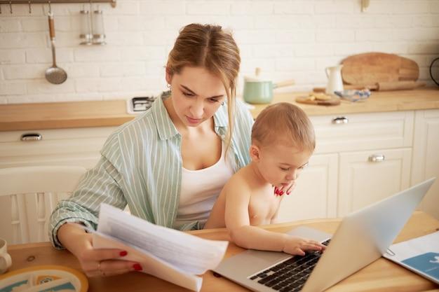Grave concentrada jovem fêmea estudando papéis nas mãos, pagando contas online, sentado à mesa da cozinha em frente ao laptop aberto segurando o filho bebê no colo. criança digitando em um computador portátil