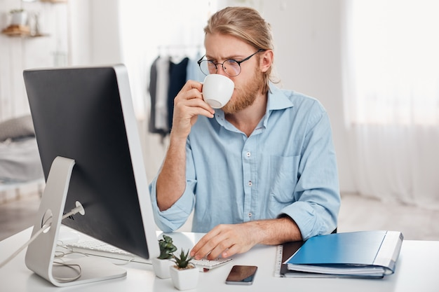 Grave concentrado no trabalhador de escritório de trabalho com cabelo loiro, barba em roupa casual e óculos, prepara o relatório, usa teclado, bebe café, trabalha durante a pausa para o almoço, senta-se contra o interior do escritório.