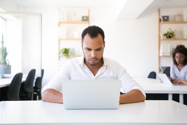 Grave empresário confiante usando laptop no escritório
