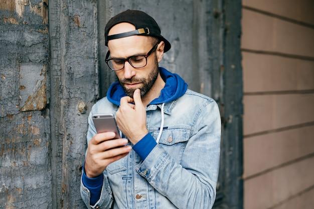 Grave homem barbudo concentrado no boné e jaqueta jeans de pé contra a parede rachada, segurando o smartphone