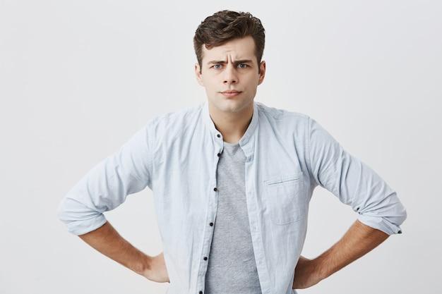 Grave homem insatisfeito com penteado elegante coloca as mãos nos quadris posando. cara bonito de olhos azuis, franzindo a testa o rosto, mostrando sua insatisfação e dipleasment