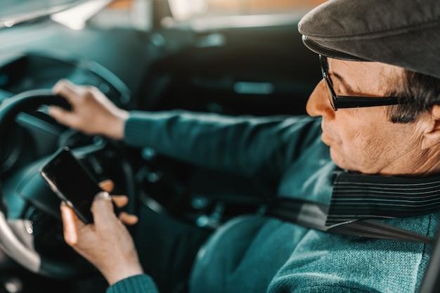 Grave homem sênior caucasiano com tampa na cabeça e óculos sentado no carro com a mão no volante e usando telefone inteligente.