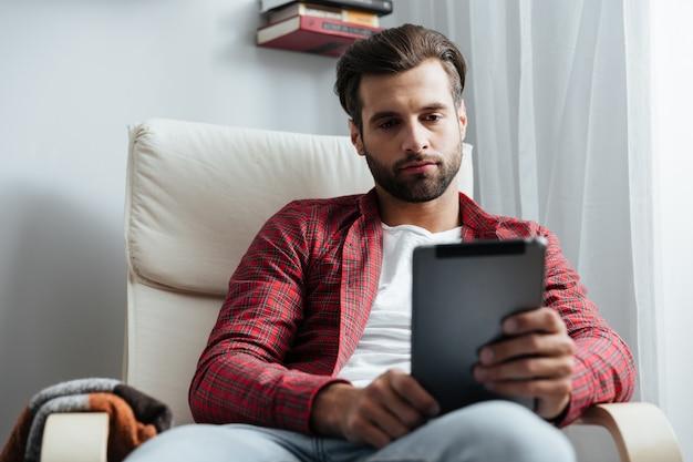 Grave jovem barbudo usando computador tablet.