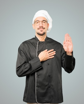 Grave jovem chef com um gesto de juramento